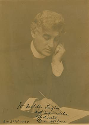 Portrait photograph of David Belasco writing with quill pen