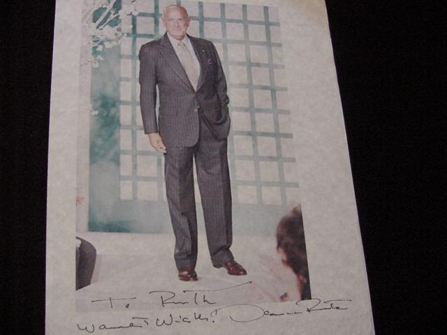 SIGNED PHOTO De La Renta, Oscar 9 x 6  color photo on 8 x10  bonded paper sheet SIGNED and inscribed by famous fashion designed Oscar De La Renta below photo. Also comes with origina