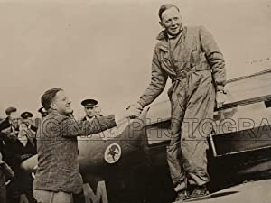 """Portrait of H. L. Brook being congratulated by Flight. Lt. """"Tommy'' Rose on his arrival..."""