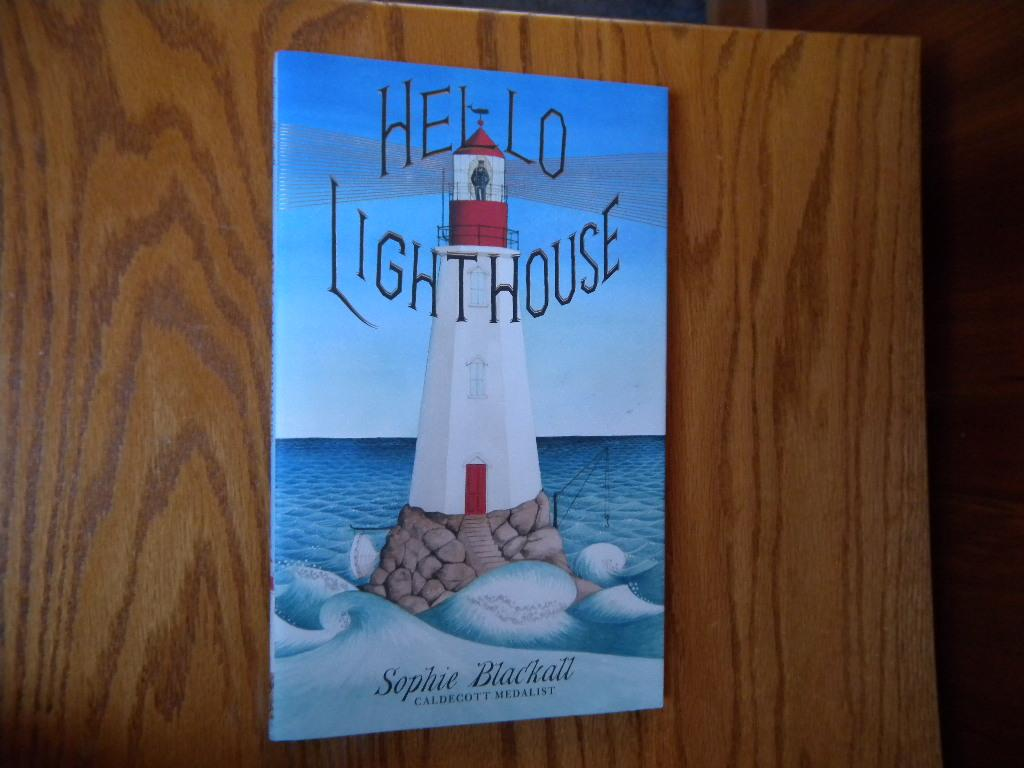 """Hello Lighthouse. (Signed with drawing). Blackall, Sophie. [Fine] [Hardcover] (Caldecott Medal). Blackall, Sophie. Hello Lighthouse. NY: Little, Brown and Company (2018). 1st Edition, 1st Printing, full number string to 1. 12 x 7 ¼. [43] pp with one fold-out illustration. Color illustrated paper over boards lettered in silver and black. Priced color illustrated dust jacket without the Caldecott Medallion. Signed by the author/illustrator on the title page. Ms. Blackall has also added a few additional touches to the title page…a drawing of a whale; the man in the Lighthouse calling 'hello"""" as does a man on the bow of the ship. In addition, a Lighthouse postcard designed by the illustrator is included. Fine copy in Fine priced dust jacket. Winner of the 2019 Caldecott Medal. Ms. Blackall also won the Caldecott Medal for her illustrations of Finding Winnie by Lindsay Mattick."""