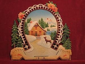 Reklamewandbild aus geprägter Pappe: Verschneites Haus mit einem Reh am See.