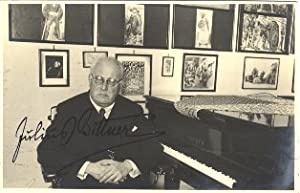 Attractive signed postcard photograph of the noted Viennese composer in a music studio, seated at...