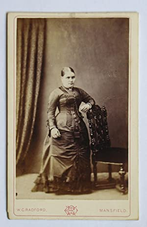Carte De Visite Photograph. Studio Portrait of a Woman Wearing a Fine Dress Beside a Chair.