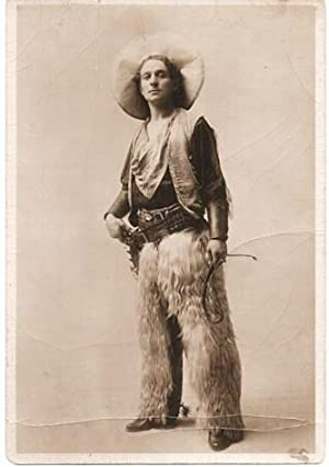 SEPIATONE STUDIO PHOTOGRAPH OF A COWBOY IN FULL REGALIA: sheepskin chaps, ten-gallon hat, vest, b...