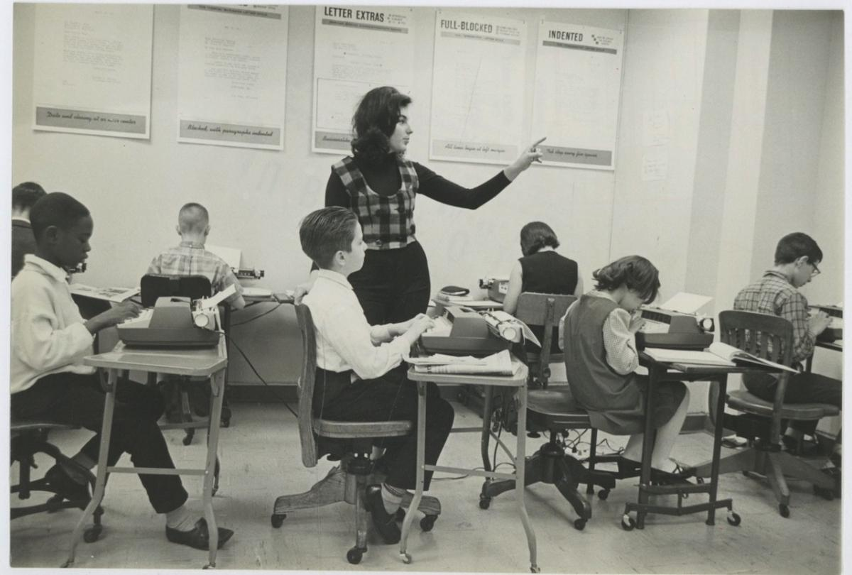 USA, Business School. Teacher Ricci Mayer and students using electric typewriters Photographie originale / Original photograph Photographie,Vintage silver print // Circa 1963 // Tirage argentique // Format (cm): 16,5x24