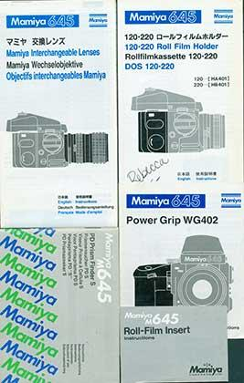 Mamiya 645 instruction manuals for the 120-220 Roll Film Holder, Power Grip WG402, and Mamiya Interchangeable Lenses + M645 manuals for the PD Prism