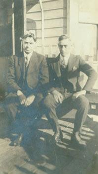Black and white photograph of two men in suits seated in front of a house.: 20th Century American ...
