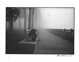 Portrait of man kneeling on bench.